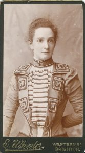 A photo of Grace as a young adult. She looks very smart here. Her jacket has spirals and stripes on. She has her hair pinned back.