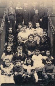 A photo of children and adults on the front steps of a building. There are some children sat at the front. The children have lots of different expressions. Some of the children are smiling, some look distracted, most of them have neutral expressions. There are some adults standing at the back of the steps. It is harder to see their faces. This is because the photo has faded at the top from age.