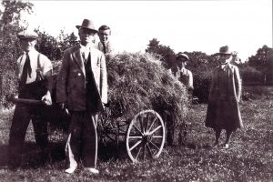 There are 3 young men pushing a wagon full of hay. They are smiling and squinting because of the sun. They are wearing shirts, suspenders and ties. Two of them are wearing caps. One man is standing in front. He is wearing a suit and a fedora. An elderly Grace stands next to them in the field. She is wearing a long coat, a wide-brimmed felt sun hat, a high collar, and wellies. It is hard to see her face but it looks like she is slightly smiling.