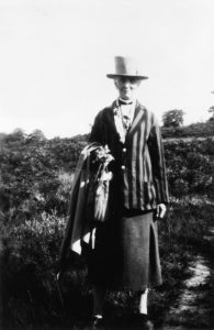 An elderly Grace is standing in a sunny field. She is wearing a stripy jacket, a three quarter-length skirt, and a big hat. She has what looks like a coat and scarf draped over one arm. She is smiling.