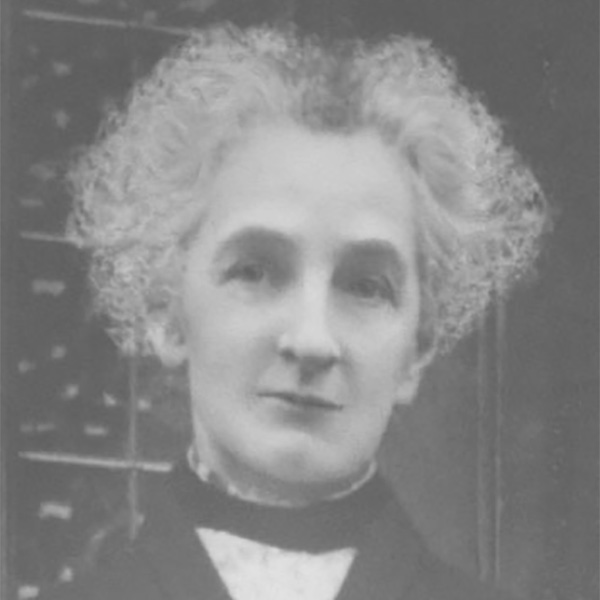 A picture of Grace Eyre Woodhead. She has grey curly hair. She is slightly smiling.