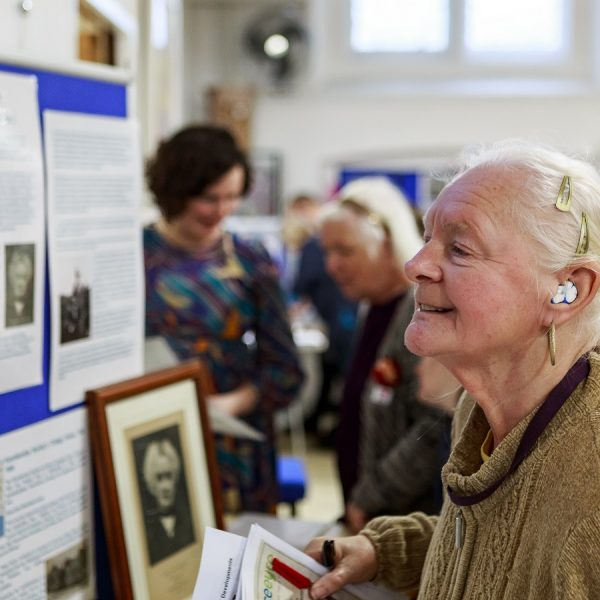 A photo of a woman. She is looking at old photographs taken at Grace Eyre.