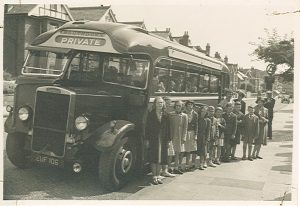 A group of children with learning disabilities standing next to a bus. This photo was taken in the 1950s. We think they were on an outing.