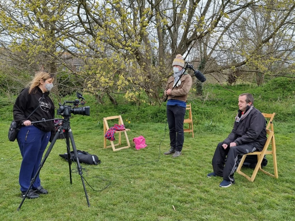 Justin and 2 volunteers learn film-making skills in the park.